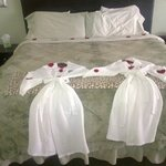 Robes and bed with rose petals and chocolates