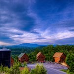 Early morning view of the smoky mountains in the background and cabins in the foreground.