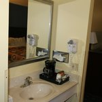 Vanity area, outside of bathroom, with a mini coffee maker. Great lighting and water pressure