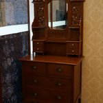 The antique dresser at the corner of the room.