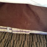 Stained, dirty valise on bed