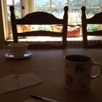 enjoying coffee while writing postcards in the dining room