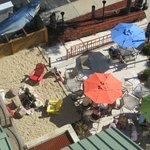 View from our balcony looking down on outside hotel restaurant with sand and fire pit