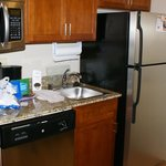 Full kitchen with fridge, microwave, stovetop, sink