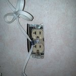 Closeup of room outlet showing cord attached despite lack of faceplate