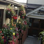Beautiful summer flowers in hanging baskets and along entrance