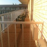 Balcony in the morning... One VERY long balcony divided only by railings.  Plastic chairs provid