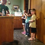 kids lining up for dinner, huge kitchen open to living and dining areas. pantry to right of kids