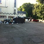 The hotel car park with a huge pile of stinking garbage next to the kitchen windows