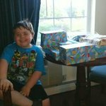 My son with his presents. Sitting at the table.