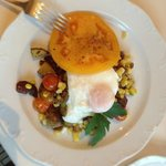 Poached egg nestles on local veggie medley