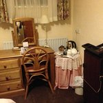 The pink table cloth and trouser press in the small room