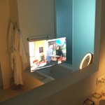 The TV embedded in the bathroom mirrow