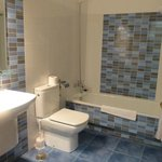 Well tiled bathroom with bathtub