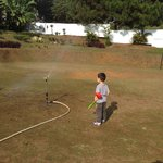 My son is amazed with the water hose sprinkling the field