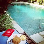 Enjoying breakfast while reading a book at the pool right infront of my room