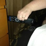 Extremely small gap between a chest of drawers and the bed as shown by the size of the tv remote