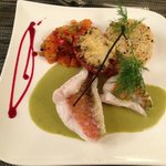Exquisite Fish with sides of tomatoes and tice