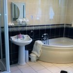 A large and inviting bath and shower at the Cranleigh