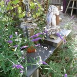 Flowers & sculptures outside of cottage in backyard
