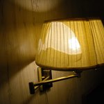 Another view of lamp next to the bed on wall