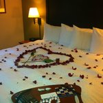 Bed was covered with rose, chocolates and also a beautiful heart made with roses