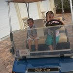our kids posing for a pic on the complimentary golf cart that comes with villa