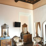High wooden ceiling, tile floor, antique furniture - a very large sitting room.