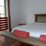 The beautiful master bedroom in the Red Rooms features a reclaimed timber queen bed.