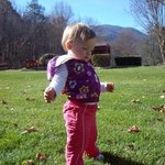 learning to walk on the front lawn, hot tub and mountains in background