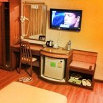 the small mini bar/tv and vanity in the room