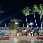 Nighttime poolside dining with a view to the stormy equatorial Atlantic ocean