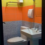clean and colorful bathroom with complimentary body wash, shampoo, rinse and toothpaste. some to