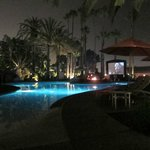 Pool area at night with fire pit and movie