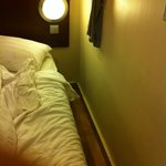 Room size, a shoe distance from bed. A dripping AC hanging above