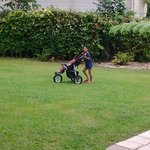 My daughter pushing my son around in the big yard.