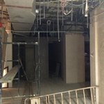 Half-finished renovations in the lobby next to lifts. Electric cables hanging down etc.