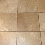 Coffee spill settled in the tile grout of the entry foyer (dark brown).
