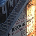 Sun rising on Welcome to Brooklyn sign