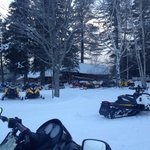 Snowmobiles around dinner time outside Lake Parlin Lodge