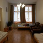 Big living room with 3 single beds, wooden flooring, big windows