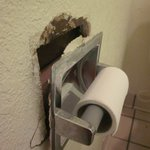 toilet paper holder falling out of wall, leaving significant hole