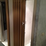 Horrible plastic concertina toilet door (no noise protection)