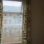 Wooden blinds with curtains that match the wall paper.