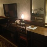 Desk area in king bed room. Quaint room but with amenities like a small fridge and large flat sc
