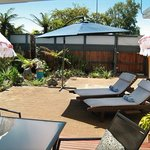 Sunny courtyard with sun-loungers, outdoor dining table, spa pool