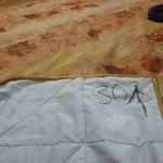 Old/stained/torn bed cover with black marker room number (of other room)