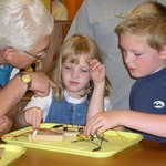 Volunteer helping guests with an electrical circuits activity.