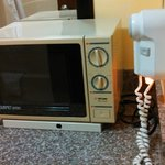 Antique microwave in bathroom beside hairdryer!
