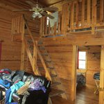 view into cabin, 4 singles up the stairs, 1 queen bed below with kitchen, wood stove